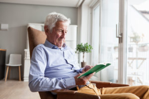 Portrait of senior man sitting on armchair at home reading a book
