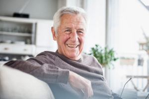 Portrait of happy senior man sitting on couch at home