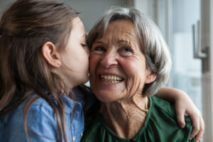 Little girl kissing her grandmother