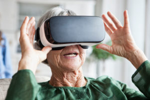 Senior woman using Virtual Reality Glasses at home