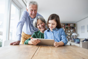 Grandparents and their granddaughter using digital tablet at home