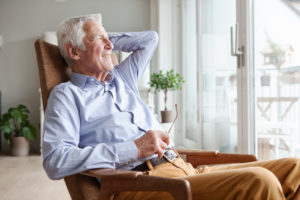 Portrait of senior man relaxing on armchair at home