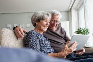 Happy senior couple sitting on the couch in the living room using digital tablet