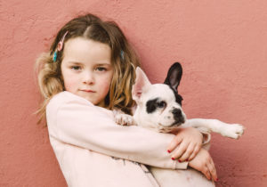 Portrait of little girl with her French bulldog