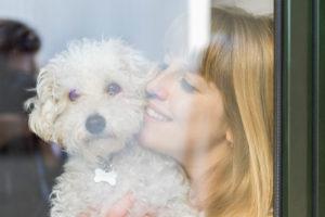 Happy woman behind windowpane cuddling her dog
