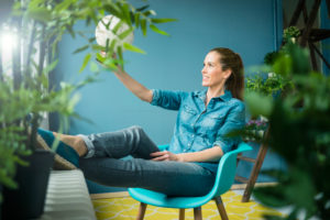 Beautiful woman sitting in her home, decorated with plants, looking at globe