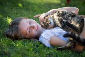 Girl lying with cat in garden