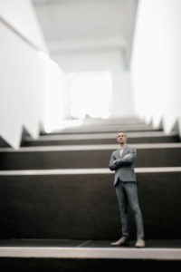 Businessman figurine standing on stairs in office
