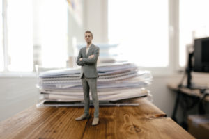 Businessman figurine standing on desk with files