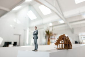 Businessman figurine standing on desk next to architectural model