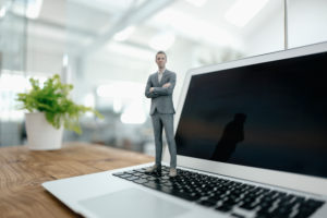 Businessman figurine standing on laptop in modern office