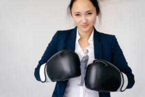 Businesswoman holding businessman figurine between boxing gloves