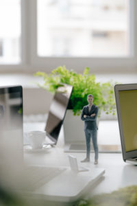 Businessman figurine standing on desk with mobile devices