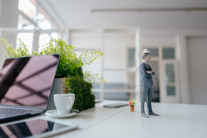Businessman figurine standing on desk, balancing a cup of coffee on top of his head