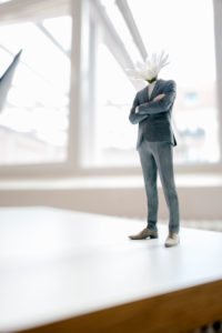 Businessman figurine with a flower head standing on desk
