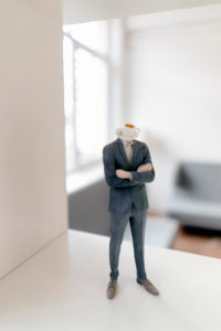 Businessman figurine with coffee cup head standing in office