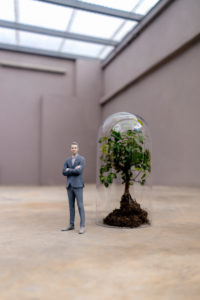 Businessman figurine standing by tree under a bell jar