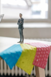 Businessnessman figurine standing on desk with tablet keyboards