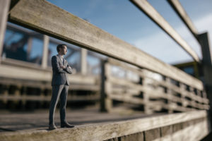 Businessman figurine standing on wooden stairs