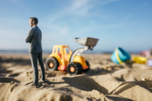 Businessman figurine standing on sand with toy digger, investment in home ownership