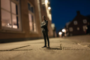 Businessman figurine standing in street in front of houses