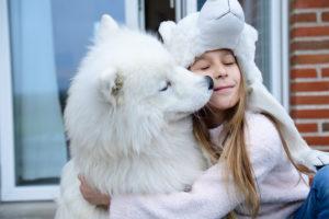 Girl hugging her dog on terrace