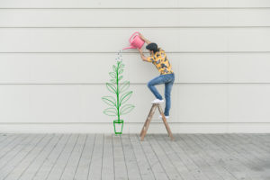 Digital composite of young man watering flower at a wall