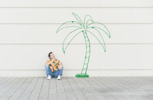 Digital composite of young man sitting at a palm at a wall