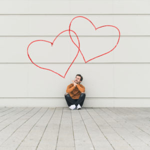 Digital composite of young man sitting at a wall with hearts