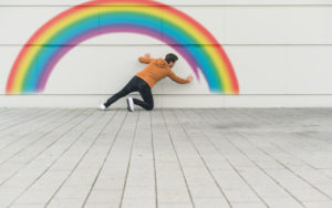 Digital composite of young man painting a rainbow at a wall
