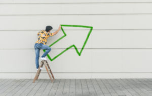 Digital composite of young man drawing an arrow at a wall
