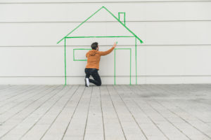 Digital composite of young man drawing a house at a wall