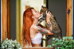 Red-haired tattooed woman with her cat at the window
