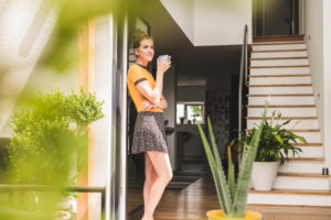 Woman holding cup of coffee leaning against terrace door at home