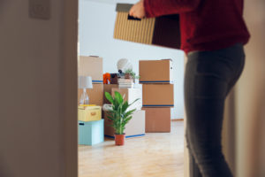 Woman carrying cardboard box in a new home