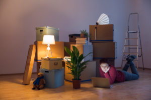 Woman using laptop surrounded by cardboard boxes in a new home