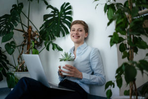 Portrait of a businesswoman with laptop sitting on the floor surrounded by plants