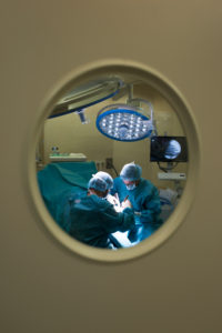 Surgeons during a surgery behind the door