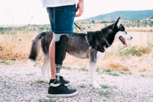 Young man wearing leg prosthesis with dog on dirt track