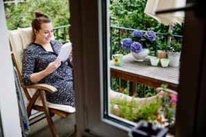 Smiling young woman sitting on balcony reading book