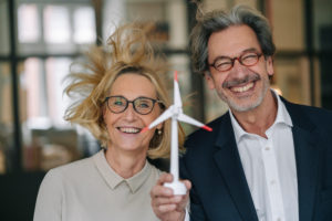 Portrait of happy businessman and businesswoman holding wind turbine model in office