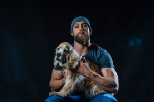 Portrait of a muscular man sitting in studio with a dog
