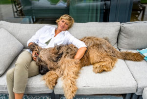 Woman relaxing with dog on terrace at home