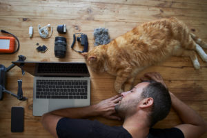 Exhausted man sleeping on table with ginger cat, laptop and photografic equipment