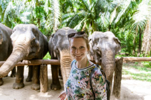 Portrait of smiling woman with elephants in sanctuary, Krabi, Thailand