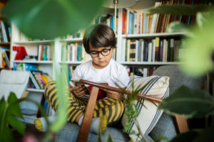Portrait of concentrated boy with glasses sitting on armchair reading book