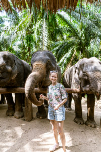 Portrait of smiling woman feeding elephants in sanctuary, Krabi, Thailand