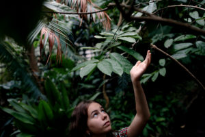 Female teenager in Botanical Garden looking up to leaves