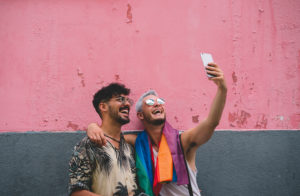 Gay couple taking a selfie in front of a pink and grey wall