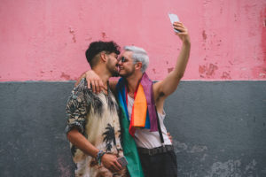 Gay couple kissing each other with smartphone in front of a pink and grey wall